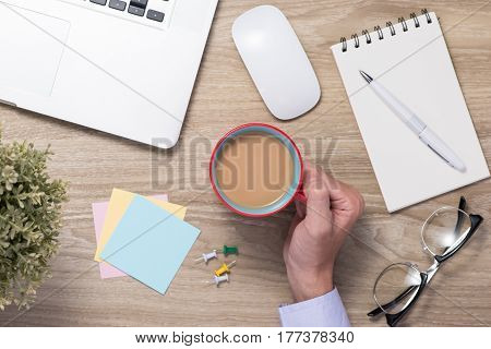 Businessman hand holding cappuchino coffee cup on table.