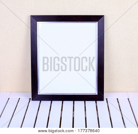 Black simple frame on white wooden table in modern interior. Framed poster mock-up
