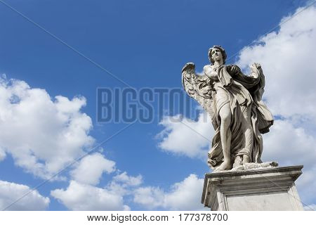 Angel statue with garment and dice on Castel Sant'Angelo Bridge with heavenly sky and copy space