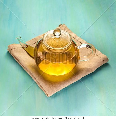 A square photo of a teapot full of tea, shot on a teal blue texture with a place for text