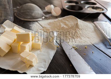 Ingredients for the dough. Eggs, flour, butter, sugar, lemon and kitchen tools on a dark wooden background. Rustic background. The process of making cakes for a cake Napoleon
