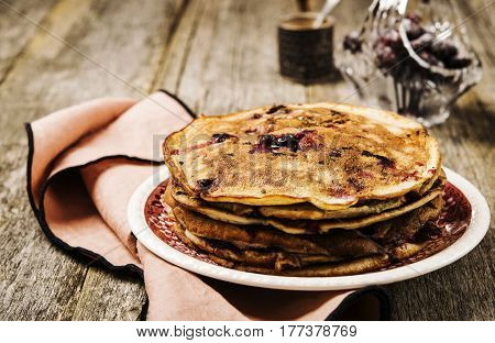 Stack of homemade freshly baked pancakes crepes with black currant berries on a rustic vintage wooden background. Healthy breakfast. Selective focus