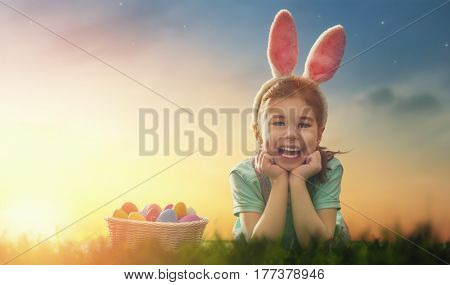Cute little child wearing bunny ears. Girl has a basket with eggs. Kid sitting on the lawn at Easter in the rays of the setting sun.