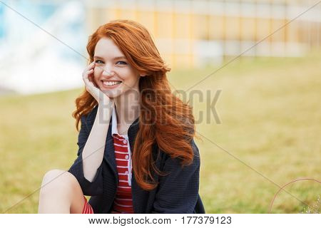 Portrait of a smiling casual red head girl sitting on the grass in park and looking at camera