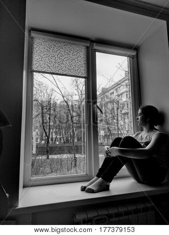 Mobile photo. Sad girl. She sits on windowsill and looks out window. Black and white photo. Film grain and artifacts for vintage style effect