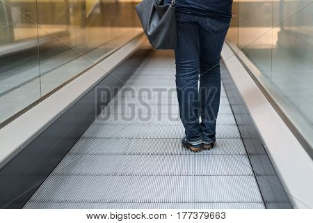 image of a woman on the escalator rear view