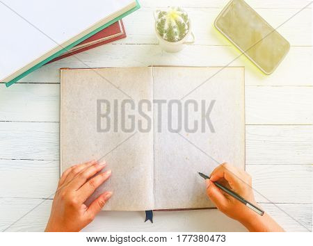 Top view of human hand writing something on old blank paper with book cactus mobile and sunlight