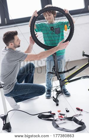 Father And Son Affixing Bicycle Wheel Together On White