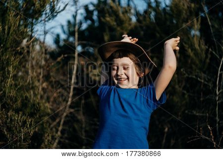 Smiling boy outdoor in summer forest. 6 years old kid in hat playing in nature.