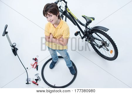 Top View Of Smiling Boy Standing Inside Tire Near Bicycle On White