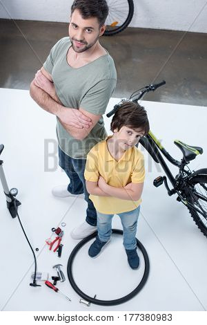 High Angle View Of Father And Son Standing Near Bicycle On White