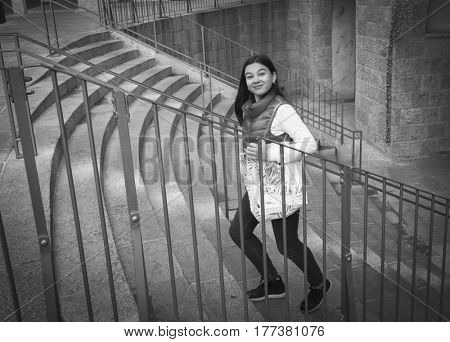 A happy girl is climbing the stairs in the park. She has a shopping bag in her hands. Black and white photo