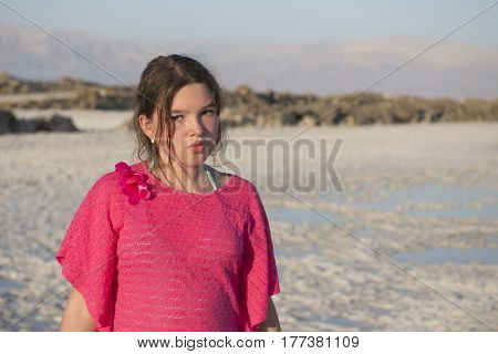 Sad teenager girl on the background of the Dead Sea (Israel).