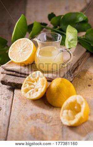 glass bowl of freshly squeezed lemon juice lemon squeezer and ripe lemons on wooden background.