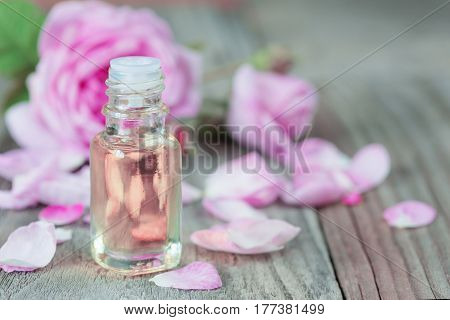 Glass vial with rose essential oil and flower of pink rose on a wooden background