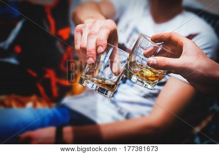 Two hands clink glasses of whiskey at homeon the couch cozy