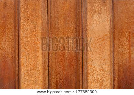 Rust on metal as a background.Orange rusty striped wall texture.