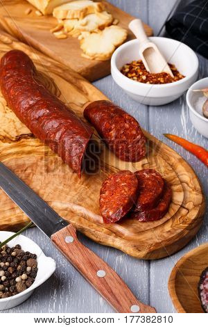 Salami with paprika on table. Rustic style.