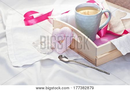 A tray with a cup of hot tea and homemade meringue in the form of a heart in bed on white textiles. Herbal tea Hot drink Love Breakfast in bed Morning