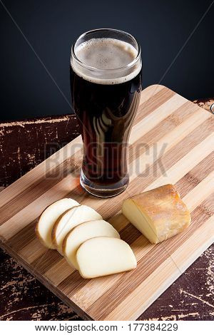 Glass With Dark Beer With Smoked Cheese On Cutting Board.