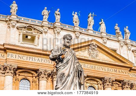 Vatican City Rome Italy. Statue of Saint Peter and Saint Peter's Basilica at background in St. Peter's Square.