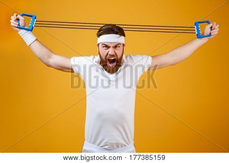 Image of screaming young sportsman make sport exercises with sport ecquipment dressed in white t-shirt standing isolated over yellow background. Looking at camera.