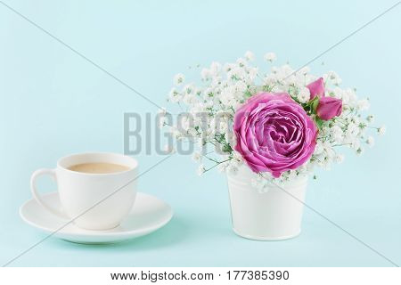 Beautiful pink rose flower and gypsophilla in vase and cup of coffee on turquoise vintage table for cozy breakfast.