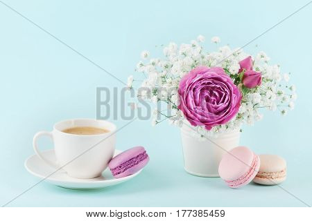 Beautiful pink rose flower and gypsophilla in vase, macaroon and cup of coffee on turquoise vintage table for cozy breakfast.