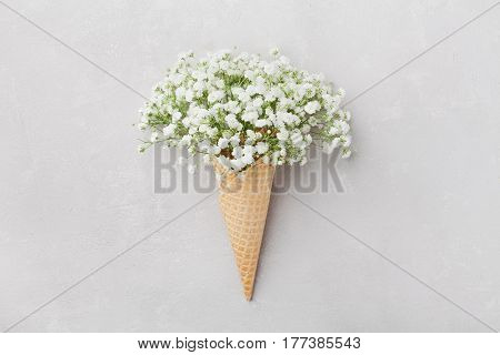 Ice cream of gypsophila flowers in waffle cone on light gray table top view in flat lay style.