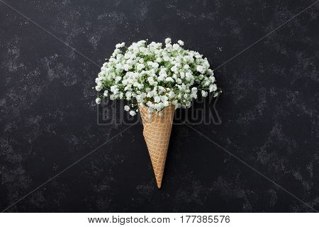 Ice cream of gypsophila flowers in waffle cone on black table top view in flat lay style.