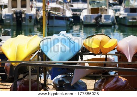 Plastic color boats dry on the background of boats and yachts