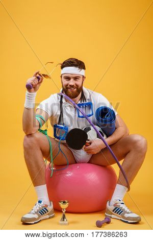 Portrait of a satisfied sports man sitting on a fitness ball and holding sports equipment isolated on a orange background