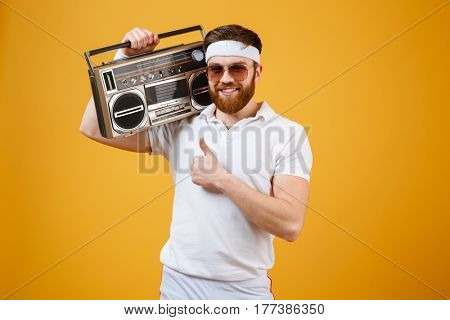 Image of cheerful young man wearing sunglasses holding tape recorder dressed in white t-shirt isolated over yellow background. Looking at camera make thumbs up gesture.