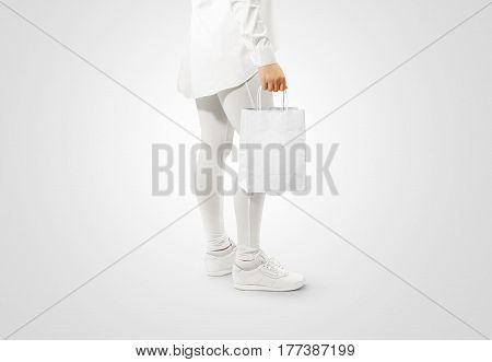 Blank white craft paper bag design mockup holding hand. Woman hold kraft textured purchase pack mock up isolated. Clear shop bagful branding template. Shopping carry package in persons arm.