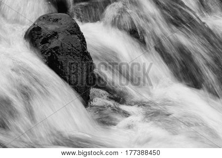 Fast flowing mountain stream and rock