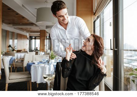 Young Woman in dress which sitting in restaurant with man behind her which looking to each other