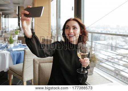 Woman in dress which sitting by the table in restaurant and making selfie on phone with wineglass in her hand