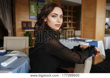 Side view of woman in dress which sitting by the table in restaurant and looking at camera