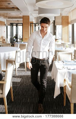 Vetical image of man in business clothes which walking in restaurant with arm in pocket