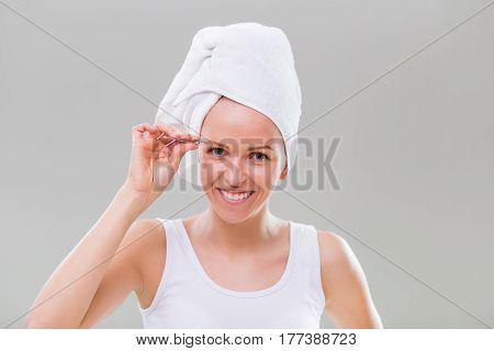 Beautiful young woman plucking eyebrows on gray background.