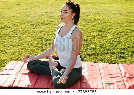 Happy peaceful young woman sitting in lotus pose and meditating on lawn