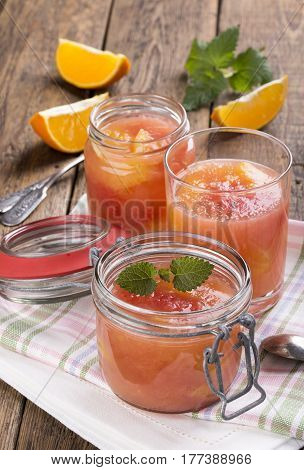 Citrus jelly in a glass jar. Homemade grapefruit orange gelatin dessert. Healthy low fat and low calorie meal.