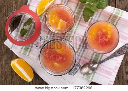Citrus jelly in a glass jar. Homemade grapefruit orange gelatin dessert. Healthy low fat and low calorie meal. Top view.
