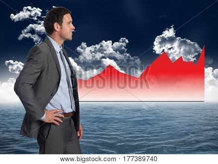 Digital composite of Businessman Standing in front of Graph against a sea and sky background