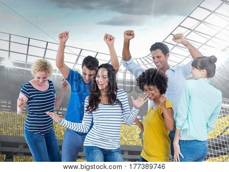 Digital composite of Happy and Cheerful Friends at Stadium Dancing and Celebratin against a Bright background