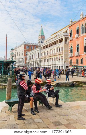 Gondoliers At A Canal In Venice, Italy