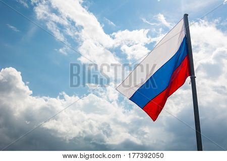Russian flag on the background of the beautiful sky
