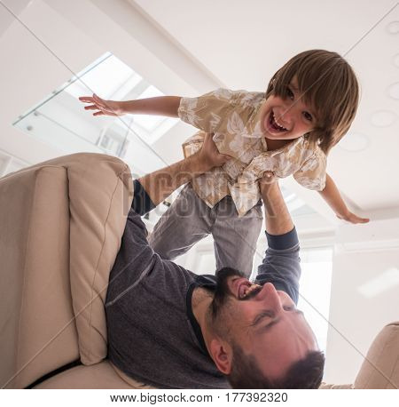 Cheerful child with father on sofa