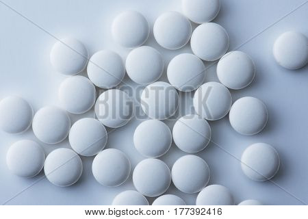 White medicine tablets or pharmaceutical pills on white background, shot from above. intentionally shot in low key, slightly bluish tone.
