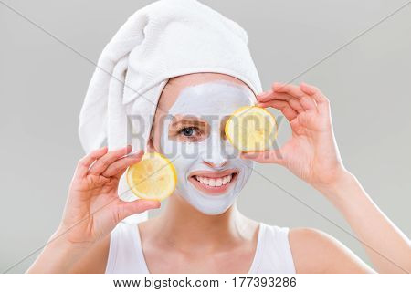 Young woman with facial mask holding slices of lemon on gray background.
